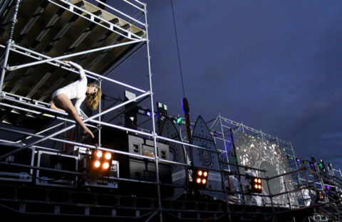 An image of an acrobatic woman using scaffold during her performance.