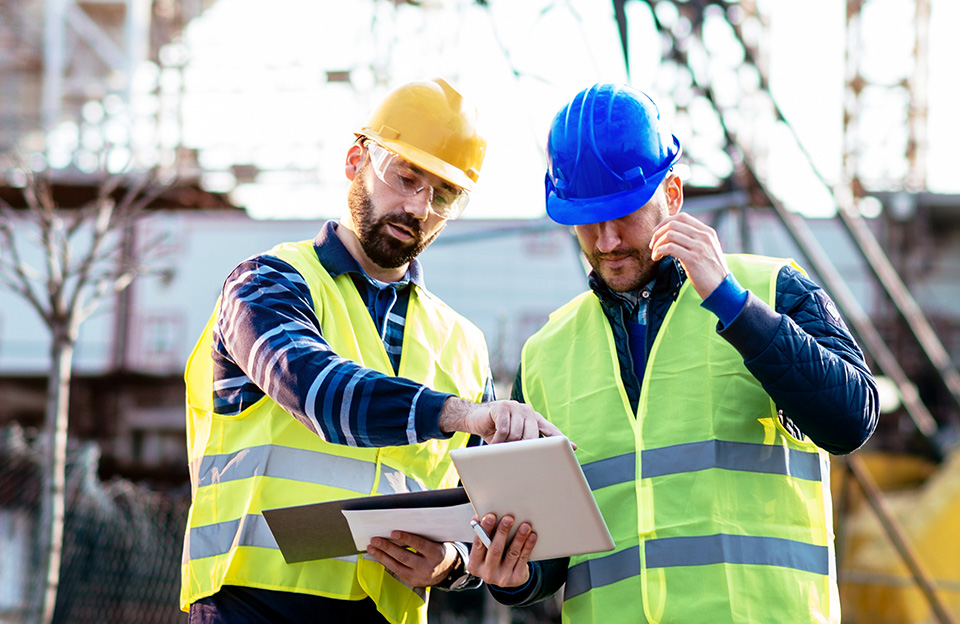 An image of two engineers in safety gear checking plans on a tablet while on site.