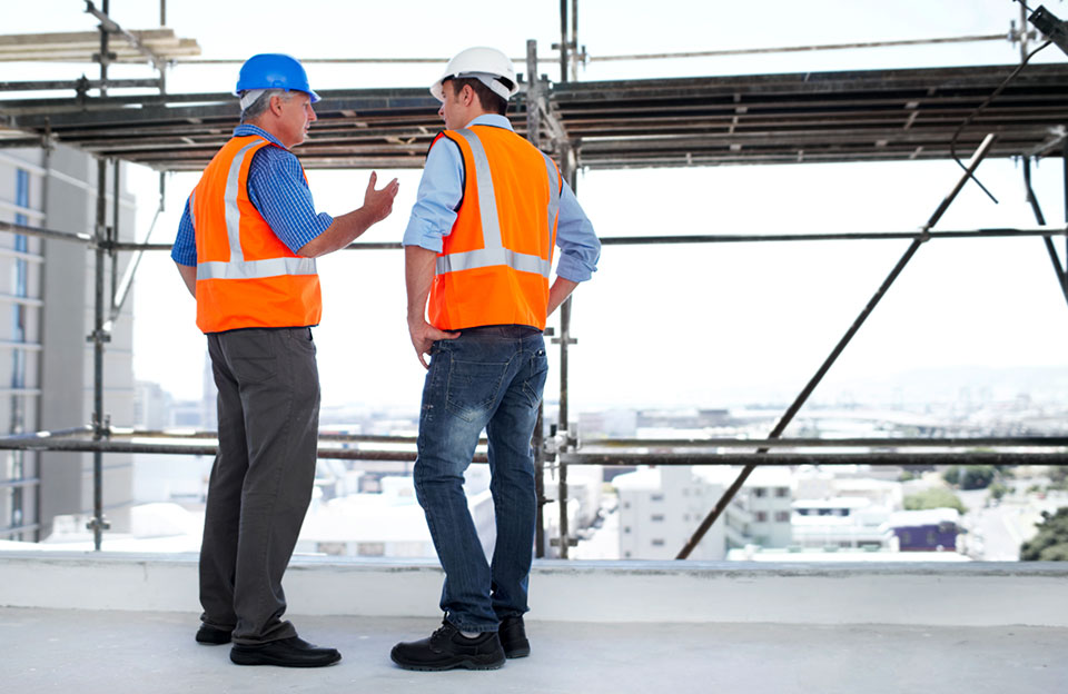 An image of two engineers in vest and hard hat discussing a scaffold challenge.